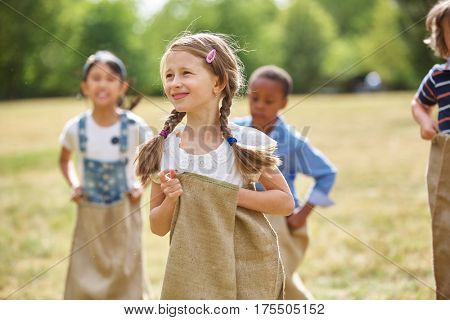 Girl with braided hair at sack race at the park
