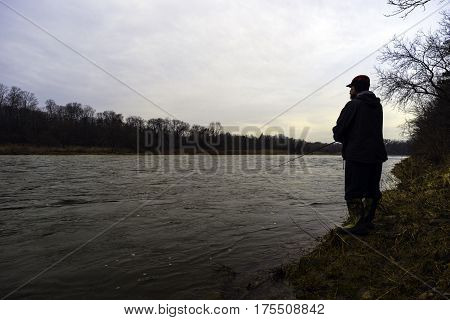 Early spring fisherman fishing off bank of fast flowing river at sunrise rugged outdoorsman