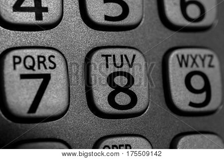 Closeup of phone number and letter buttons on cordless device metallic gray and black