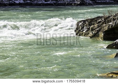 River rapids with white waves flowing snow and ice on rocky riverbank