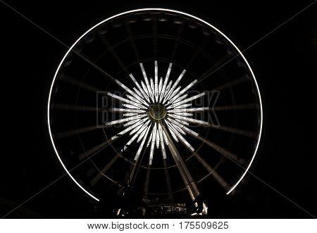 White star ferris wheel brightly lit at amusement park at night dark background