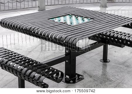 Abandoned game of checkers being played on outdoor built in game table with rocks called on account of rain