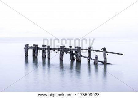 Rustic broken pier wooden posts standing in calm blue lake waters