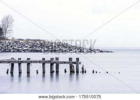 Broken pier wooden posts in front of rocky shoreline with bench large sky with space for text