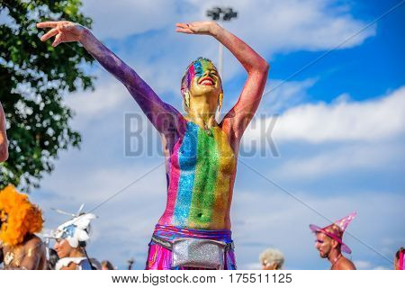 RIO DE JANEIRO, BRAZIL - FEBRUARY 28, 2017: Smiling naked woman rainbow of Bloco Orquestra Voadora in support of feminism with body-art and walking on stilts at Carnaval 2017