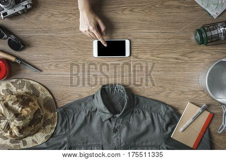 Hand Using Phone Surrounded With Travel Stuff On Top View, Camping Stuff On Wood Background(green Sh