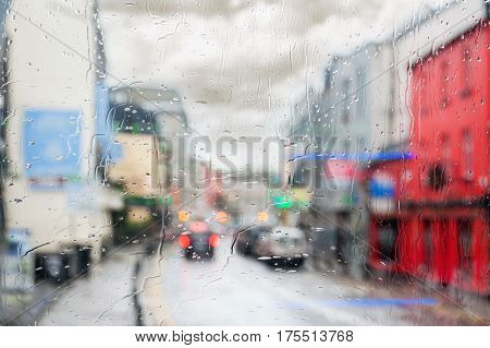 Rainy weather and a city. raindrops flow on window glass. buildings and cars are barely visible through the rainy mist