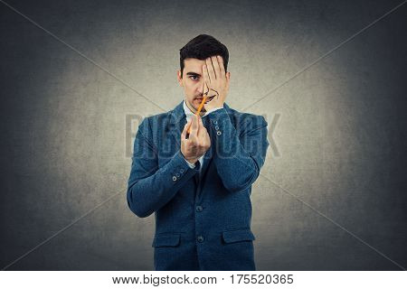 Portrait of a businessman hiding half face with his hand trying to draw a big smile. Create new identity grey wall background.