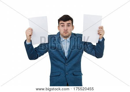 Confused young businessman holding two white papers in hands isolated on white background. Human emotion face expression life perception concept.