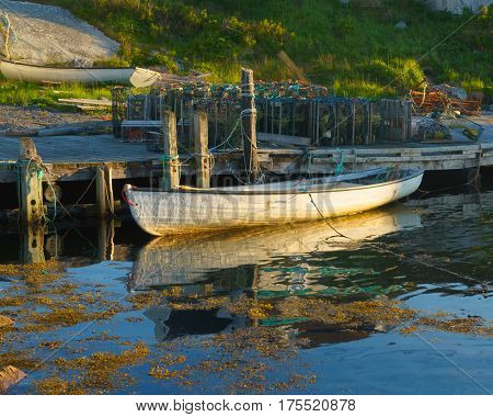 The golden hour evening light falls on a row boat in Peggy's Cove, Nova Scotia, Canada
