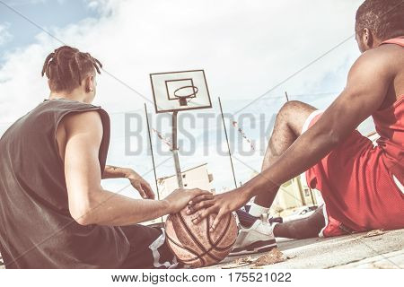 basketball players sitting on ground relaxed with the ball
