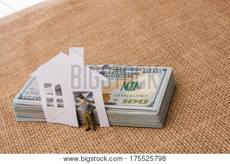 Paper House And A Man Figurine Beside Us Dollar Banknote