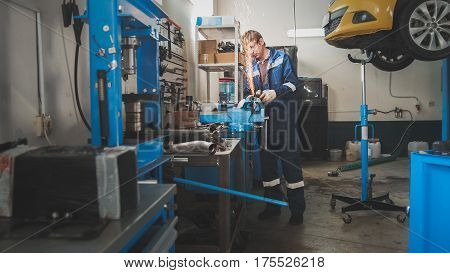 Worker male caucasian grinding metal construction with a circular saw - car auto workshop, horizontal