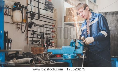Car auto workshop - worker male caucasian grinding metal construction with a circular saw, horizontal