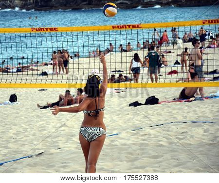 Sydney Australia - Feb 5 2017. Girl in bikini playing beach volleyball on Coogee beach. Women and men having fun. Recreational volley ball game in summer living healthy active sport lifestyle.