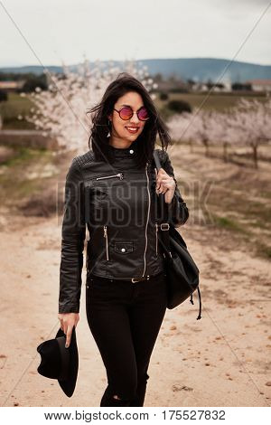 Brunette woman with leather jacket walking on a path with flowered almond trees