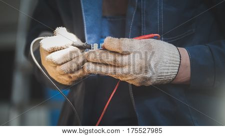 Mechanic works with car electrics - electrical wiring, close up