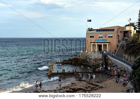 Sydney Australia - Feb 5 2017. Coogee Surf Life Saving Club and swimming pool with ocean view in summer time. People relaxing swimming and sun bathing on Coogee beach.