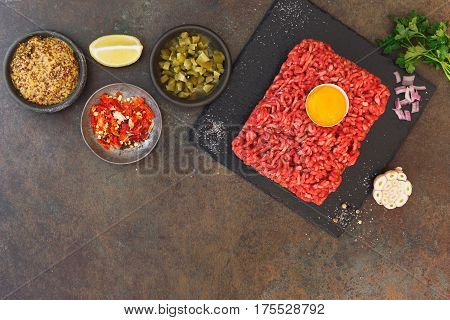 Ingredients for steak tartare on rustic textured background  Top view, blank space