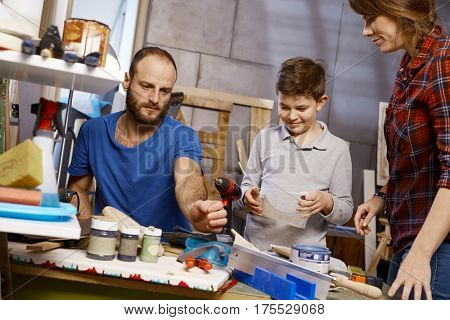 Family tinkering together in workshop.