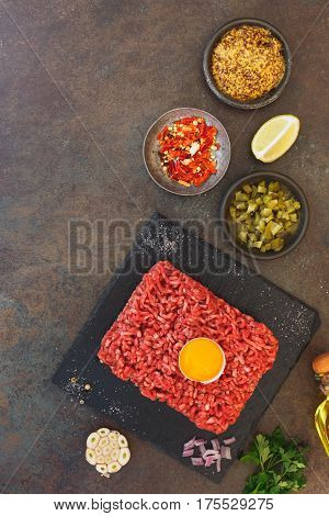 Beef tartare with an egg yolk and other ingredients on rustic textured background  Top view, blank space