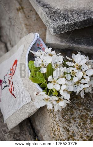 flowering branches in a makeshift purse with embroidery