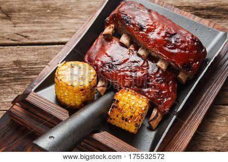 Delicious grilled pork ribs with corn served on shovel, top view. Restaurant menu photo. Chinese cuisine.