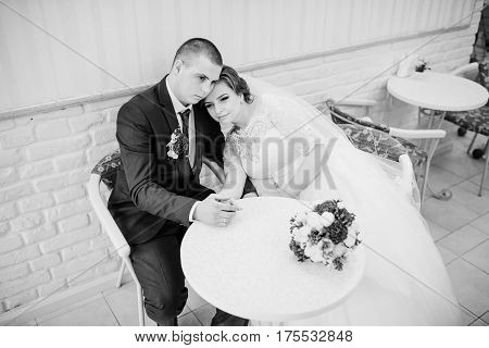 Wedding Couple Sitting At A Table In A Cafe And Holding Hands. Black And White Photo.