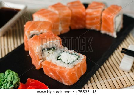 Appetizing and fresh set of rolls with salmon, philadelphia cheese served on black slate on restaurant table. Japanese sushi, healthy food, closeup.