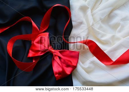 red bow and red silk ribbon on a black and white background