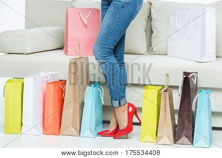 Low section of young woman in red high-heeled shoes posing near shopping bags