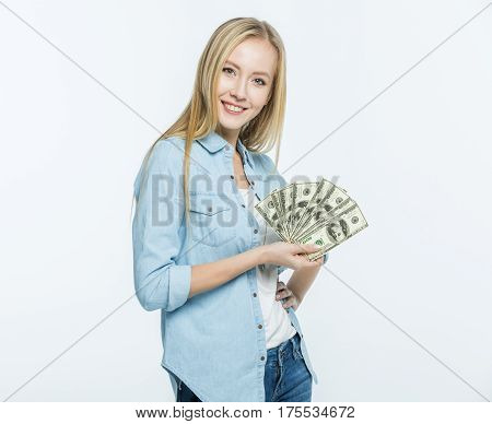 Attractive young woman holding dollar banknotes and smiling at camera