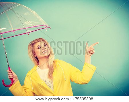 Woman Wearing Raincoat Holding Umbrella Pointing