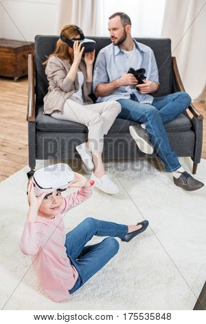 Family with one child using virtual reality headsets in cozy room