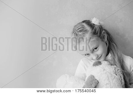 Smiling little girl holding a toy dog in the light background ( black and white )