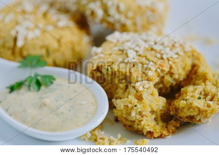 Falafels coated with white sauce, close up.