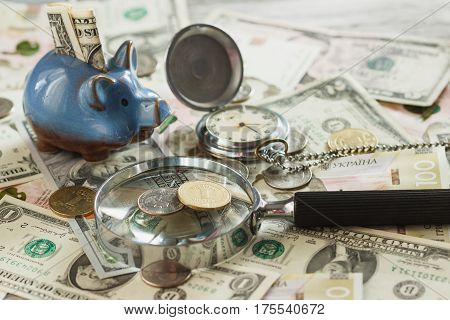 Coins And Banknotes With A Piggy Bank, Clock And Magnifying Glass