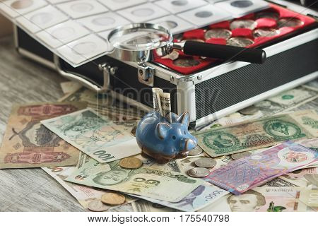 Coins And Banknotes In The Box, With A Magnifying Glass And Piggy Bank