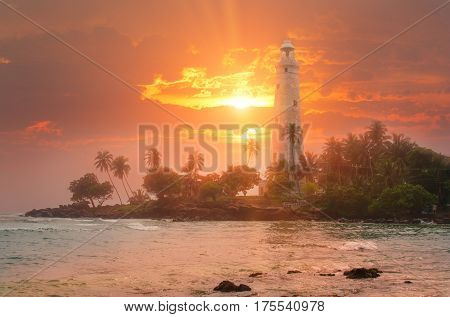 White lighthouse Dondra and tropical palm trees against the background of a fantastic sunset Sri Lanka island near Matara.