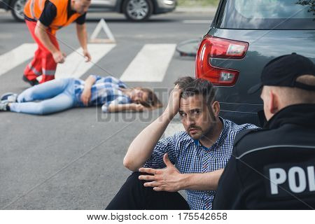 Shocked driver talking to a policeman while paramedic taking care of the casualty of car accident