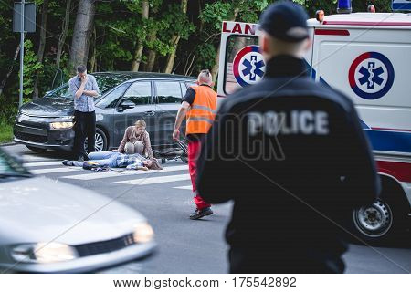 Car crash witness helping an unconscious victim with paramedic on his way