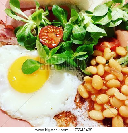 Morning Breakfast with fried egg, baked beans, bacon and salad