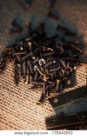 Door hinges and screws made of dark metal on a dark background of burlap. The atmosphere of workshop