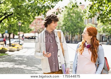 Young male and female college students talking while walking on footpath