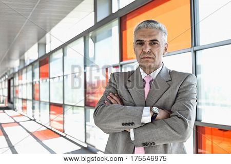 Portrait of confident middle aged businessman at railroad station