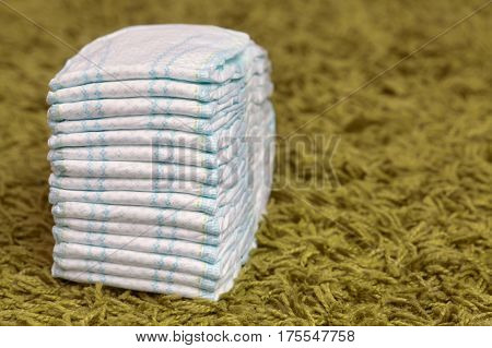 Stack of diapers or nappies on green carpet closeup