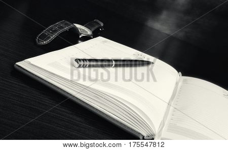 Opening the daily log with pages without records lies on a table. On a notebook the ball-point pen lies. Nearby the watch lies. Horizontal format. Small depth of sharpness. Мonochrome. Indoors. Photo.