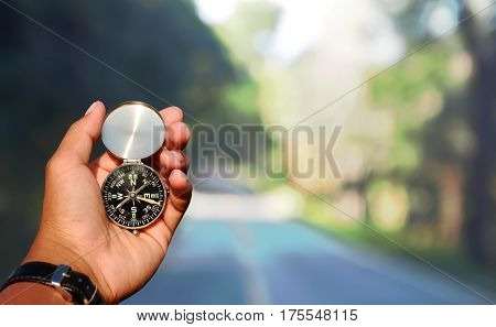 Man hand with a black and silver compass in green mountain soft blur.