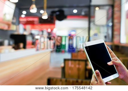Hand hold and touch screen tablet,with abstract blur coffee shop.