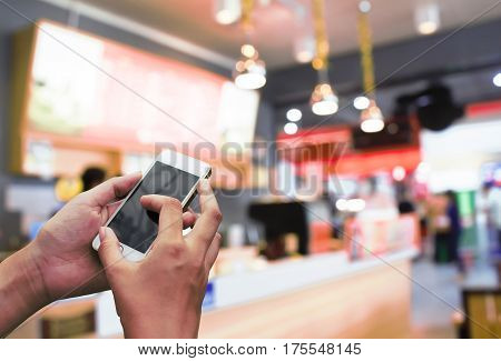 Man use mobile phone, blur image of restaurant in the mall as background.